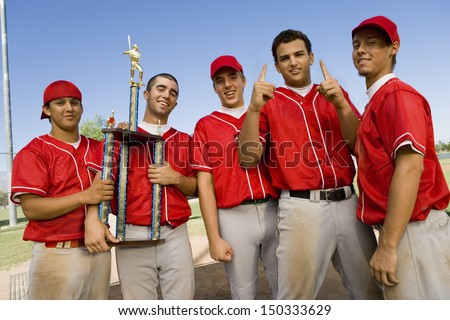 Portrait of successful baseball team with trophy on field - stock photo