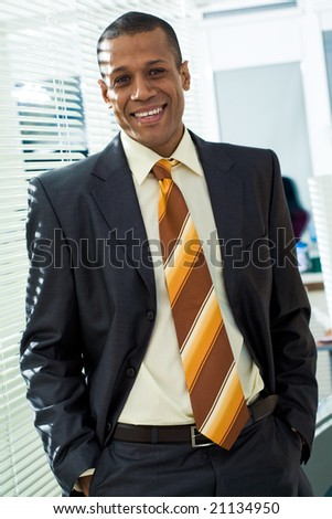 Portrait of successful boss looking at camera with smile in office - stock photo