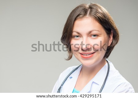 Portrait of successful brunette doctor on a white background - stock photo