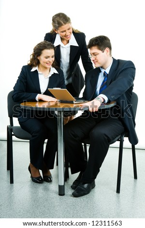 Portrait of successful business group interacting at working meeting and looking at laptop monitor