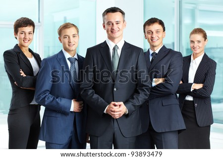 Portrait of successful business group looking at camera with confident man at foreground - stock photo
