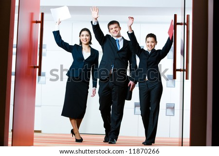 Portrait of successful business group standing at the door of conference hall with raised hands greeting their partners - stock photo