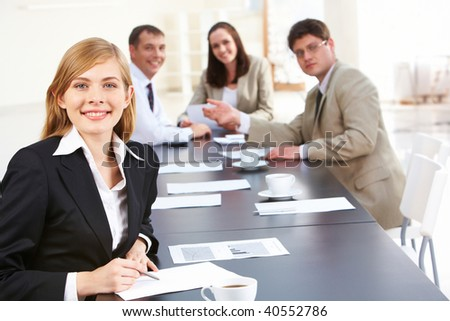 Portrait of successful business lady looking at camera on background of her colleagues