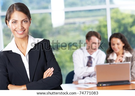 Portrait of successful business lady looking at camera with smile on background of her partners at work