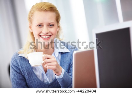 Portrait of successful business lady with cup looking at camera