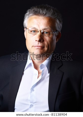 Portrait of successful business man standing on black background - stock photo