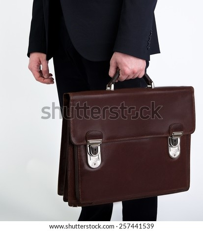 Portrait of successful business man with bag in grey background and space for text, Closeup Of Businessman Holding Briefcase Going To Work, man walking with bag,Business man hands with briefcase - stock photo