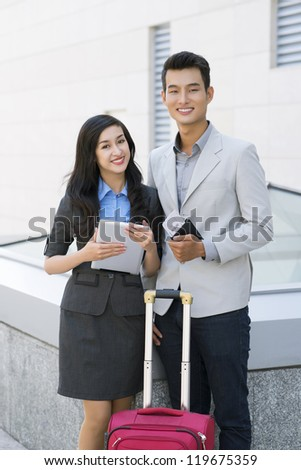 Portrait of successful business partners taking business trip - stock photo