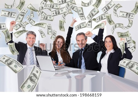 Portrait of successful business people with money rain in conference room - stock photo