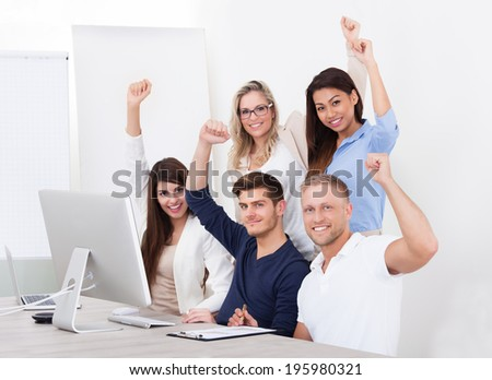 Portrait of successful business team with arms raised at desk in office - stock photo