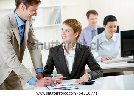 Portrait of successful businessman consulting pretty employee in working environment