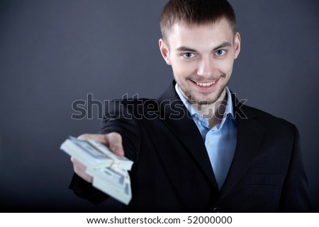Portrait of successful businessman giving money to you - stock photo