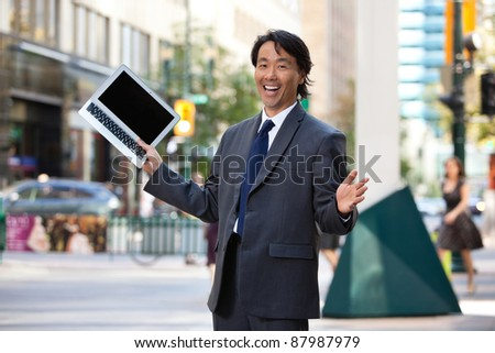 Portrait of successful businessman holding laptop and laughing - stock photo