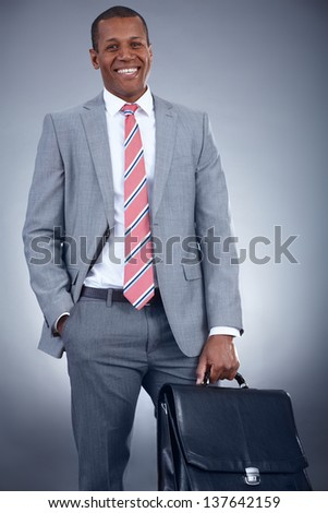 Portrait of successful businessman in suit holding briefcase - stock photo