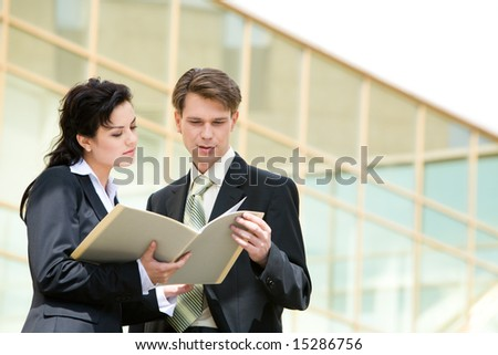 Portrait of successful businesspeople discussing a project near a office building - stock photo