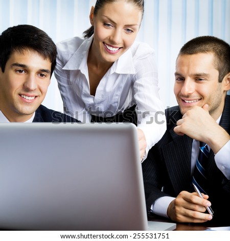 Portrait of successful businesspeople working with laptop at office