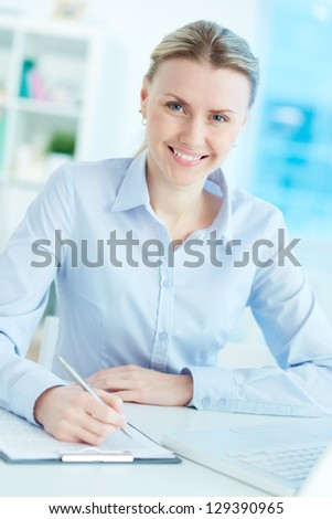 Portrait of successful businesswoman at workplace looking at camera - stock photo