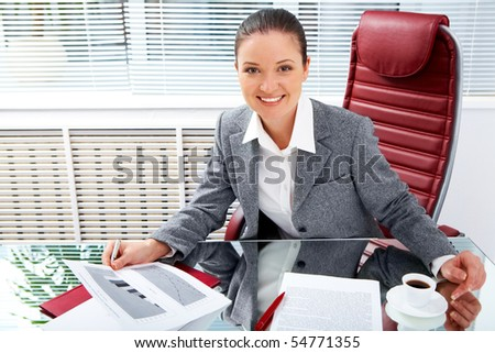 Portrait of successful businesswoman holding document while looking at camera with smile in office - stock photo