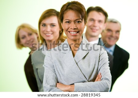 Portrait of successful businesswoman looking at camera with several employees behind