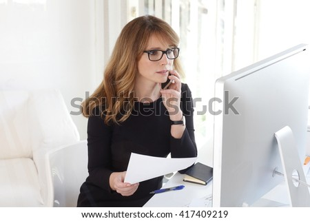 Portrait of successful businesswoman using her mobile while sitting at desk and working on computer.