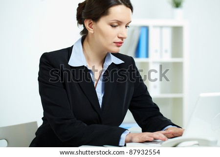 Portrait of successful businesswoman working with laptop in office - stock photo