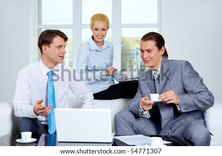 Portrait of successful co-workers sharing their ideas near laptop at meeting - stock photo