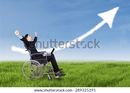 Portrait of successful disabled entrepreneur sitting on wheelchair on the meadow while celebrate his victory - stock photo