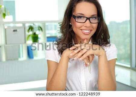 Portrait of successful female looking at camera in office - stock photo