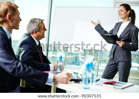 Portrait of successful female presenting her project at seminar or conference - stock photo