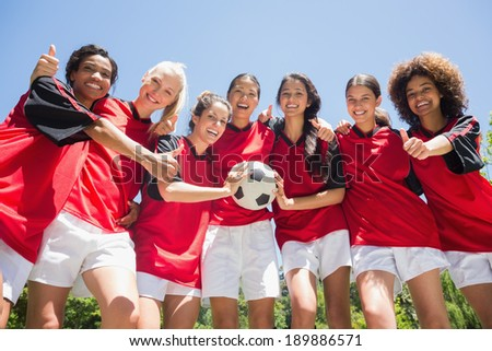 Portrait of successful female soccer players gesturing thumbs up against clear blue sky - stock photo