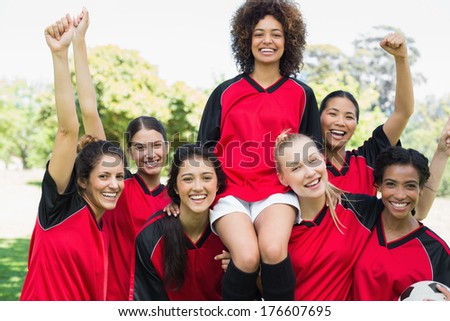Portrait of successful female soccer team at park - stock photo