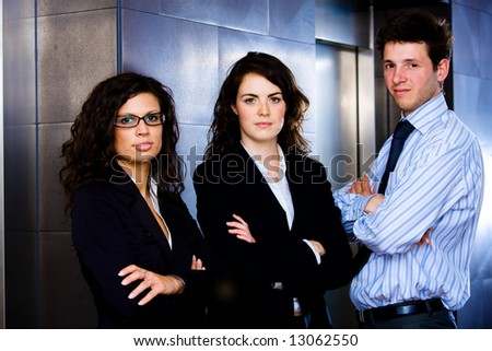 Portrait of successful happy business team posing at office lobby in front of elevator. Dark background.