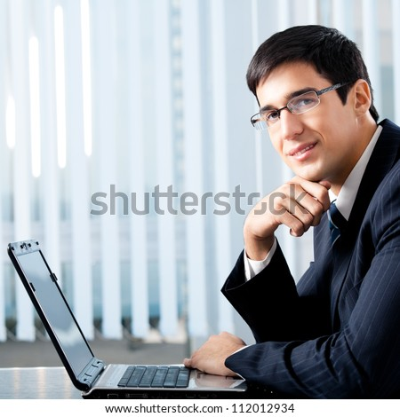 Portrait of successful happy smiling business man working with laptop at office, with copyspace