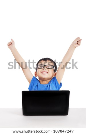 Portrait of successful little student with laptop expressing his success - stock photo