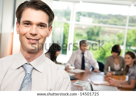 Portrait of successful manager looking at camera on the background of talking people - stock photo