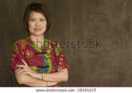Portrait of successful middle aged Asian woman with her arms crossed - stock photo