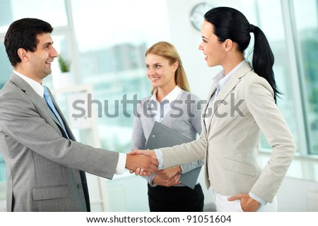 Portrait of successful partners handshaking after signing contract