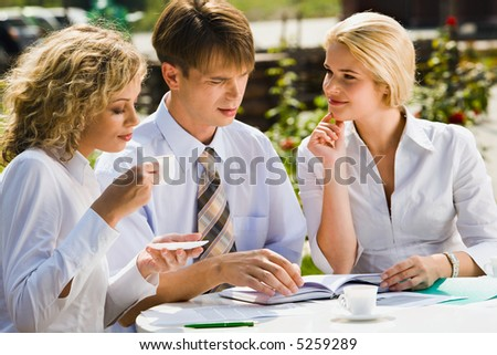 Portrait of successful partners sitting at the table in street cafe discussing new plan at lunch - stock photo