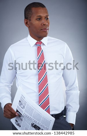 Portrait of successful professional in formalwear holding newspaper - stock photo