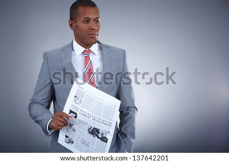 Portrait of successful professional in suit holding newspaper - stock photo