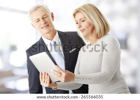 Portrait of successful sales team working with digital tablet while standing at office. Teamwork. - stock photo
