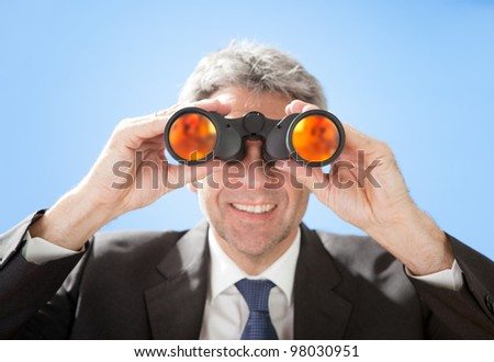 Portrait of successful senior businessman looking through binoculars on sky background