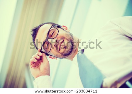 Portrait of successful smiling business man with glasses - stock photo