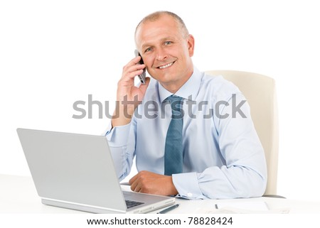 Portrait of successful smiling businessman sitting behind table - stock photo