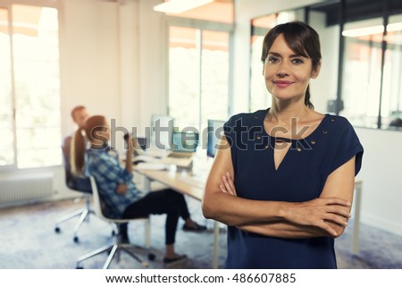 Portrait of successful woman boss in modern office space. Looking at camera. Employees in background.