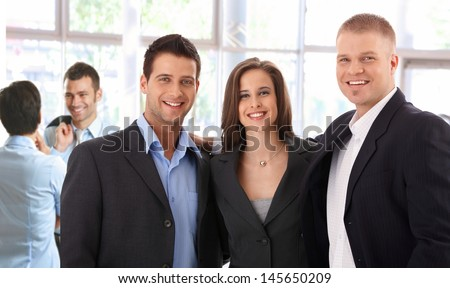 Portrait of successful young business team standing at bright office, smiling happy, looking at camera. - stock photo