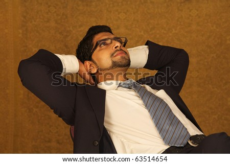 Portrait of successful young businessman relaxing on chair - stock photo
