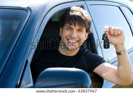 portrait of successful young happy man showing the keys sitting in new car - stock photo