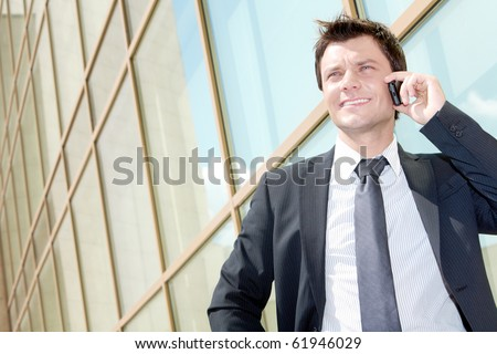 Portrait of successful young man calling on cellular phone outside - stock photo