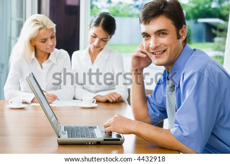 Portrait of successful young smiling businessman looking at camera in the office